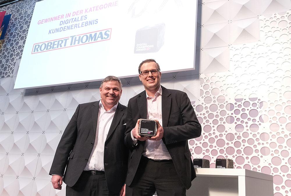 Vladimir Sizikov, Innovationsmanager bei THOMAS (rechts) freut sich mit Laudator Peter Flick, Vice President Sales Mobile Corporate Customers, Telekom Deutschland GmbH über die Auszeichnung.